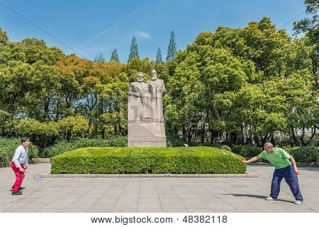 SHANGHAI - APRIL 7: two people exercising badminton in front of marx and engels statue in fuxing park on april 7th, 2013 in Shanghai
