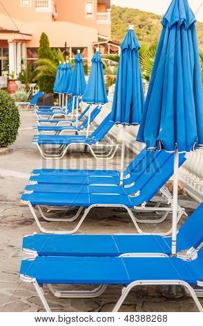 Blue Lounge Chairs And Umbrellas By The Pool