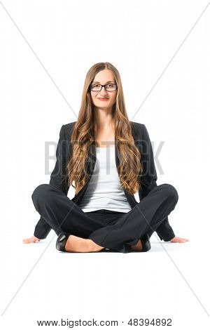 Young business woman with glasses in front of white background, sitting on the floor, maybe she is a businesswoman or laywer