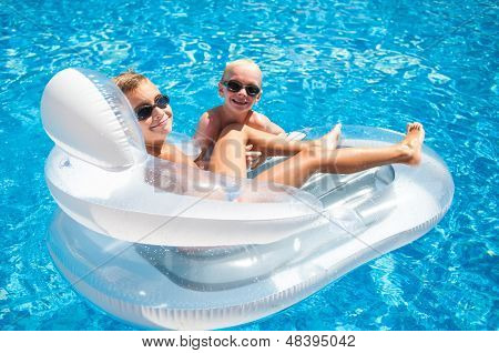 Two Boys Having Fun Playing On A Floating Mattress In A Swimming Pool