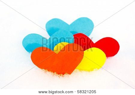 Five paper colored heart shapes in snow