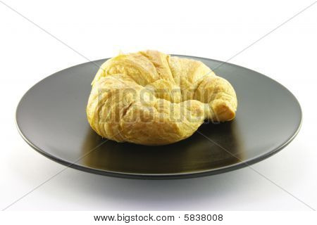 Croissant On A Black Plate