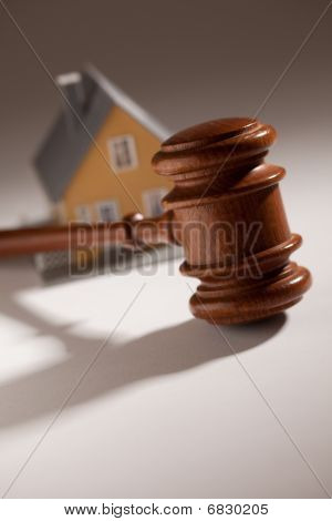 Gavel and Model Home on Gradated Background with Selective Focus. poster