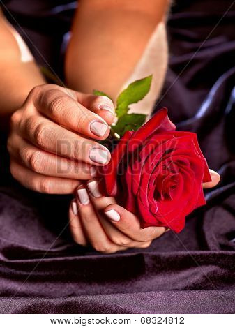 Female hand with red rose flower in black dress.Symbol funeral and luxury