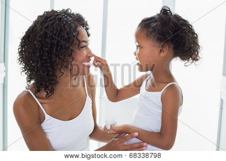 Cute daughter putting face cream on mothers nose at home in the bathroom