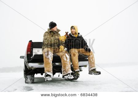 Two Men Having A Beer On Truck
