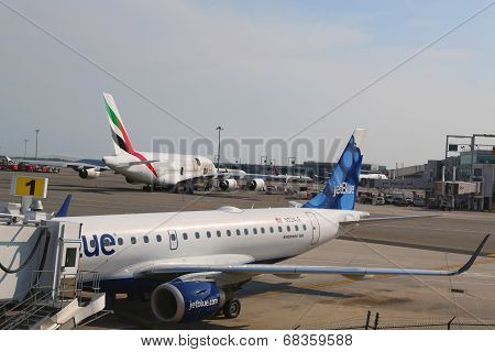 JetBlue Embraer 190 aircraft at the gate at the Terminal 5 and Emirates Airline Airbus A380 at JFK