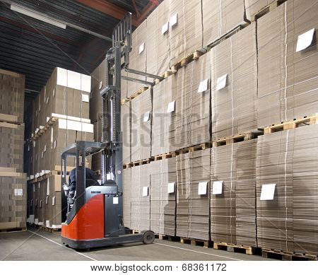 Reach truck forklift lifting a pallet from the top shelf in a large warehouse.