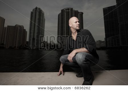 Handsome bald headed mature man posing by the bay with buildings in the background poster