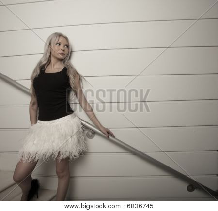 Attractive young blond haired female posing at night poster