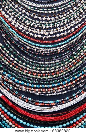 Colorful necklaces made from glass beags and pearls poster
