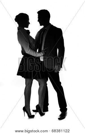 Silhouettes of a fashionable loving couple facing each other in an intimate embrace with the woman wearing a flared miniskirt and stilettos, on white