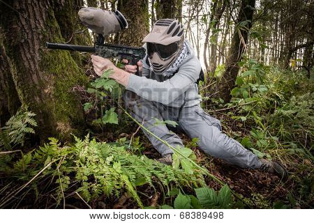 active paintball sport player in the forest with protective clothing