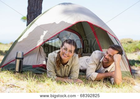 Outdoorsy couple smiling at camera inside their tent on a sunny day