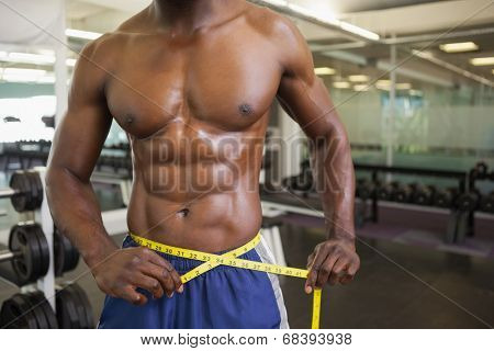 Close-up mid section of a muscular man measuring waist in gym