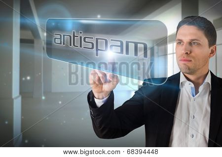Businessman pointing to word antispam against screen in room with sparks