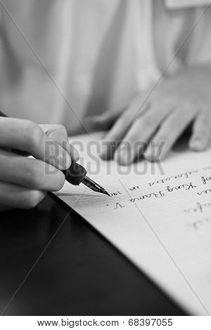 Retro effect faded and toned image of a girl writing a note with a fountain pen antique handwritten
