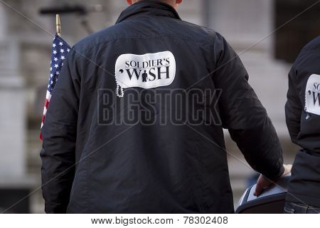 NEW YORK - NOV 11, 2014: A US vet wearing a jacket that says Soldiers Wish carries the American Flag in the 2014 America's Parade held on Veterans Day in New York City on November 11, 2014.