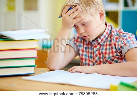 Pensive little boy concentrating on subject of lesson poster