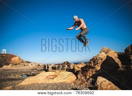 man performs freerunning jump on stones