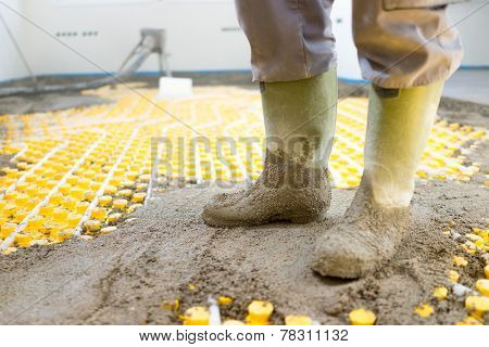 Plasterer at indoor concrete cement floor topping with float