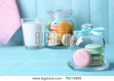 Gentle colorful macaroons in glass jell jar, milk glass and towel on color wooden table background