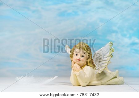 Dreaming angel on a blue background: greeting card for death, christening or communion.