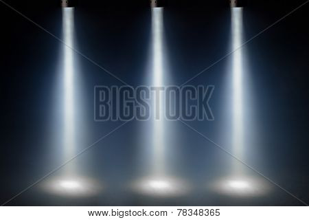 three blue spot lights on stage