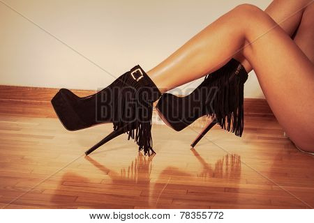 long slim woman legs in black ankle high heel fringe boot indoor shot on parquet against wall retro colors