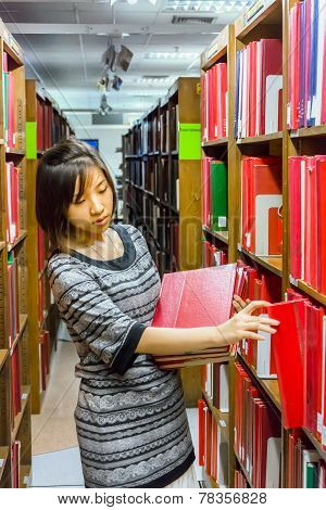Thai College Girl Is Selecting Book From The Shelf .