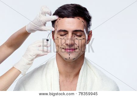 Man with closed eyes at plastic surgery with syringe in his face poster