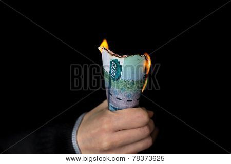 Person grips pack of burning Russian banknotes with nominal value of one thousand rubbles poster