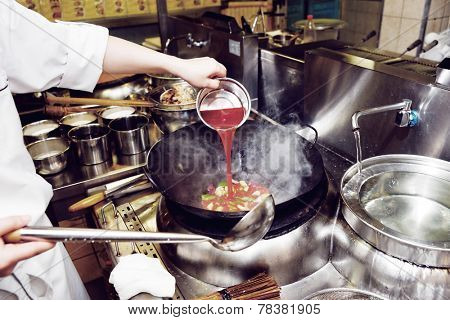 Chef is pouring sour sauce in wok, toned
