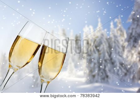 Glasses with champagne , snow cowered pine trees in the background