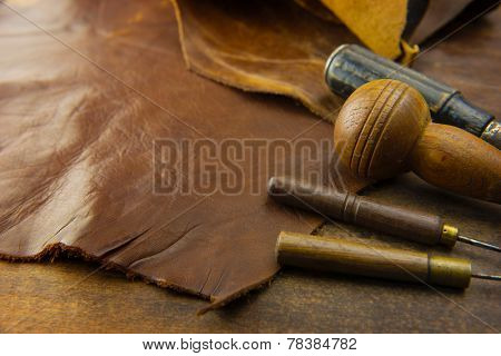 Leather craft. Leather and leather crafting tools on a work table.