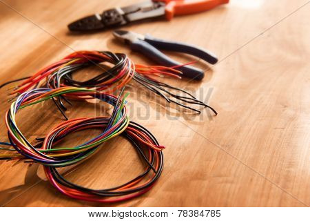 Colored cables or wires and a wire cutter tools on a wooden work desk, with by-the-window type lighting environment.