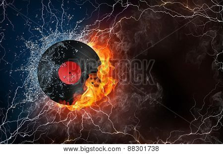 Phonograph record on fire and water with lightening around on black background. Horizontal layout with text space.