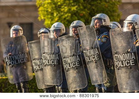 ATHENS, GREECE - APR 16, 2015: Riot police with their shields, take cover during a rally in front of the Athens University, which is under occupation by leftist protesters and anarchist groups.