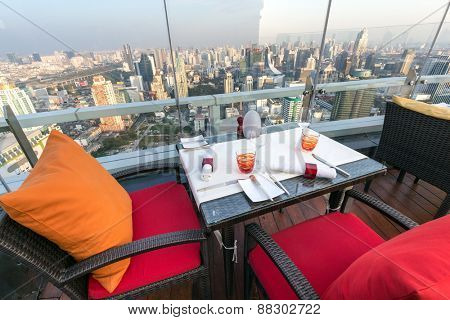 BANGKOK, THAILAND, JANUARY 14, 2015: Restaurant table with view on the cityscape at the Red Sky Rooftop of the Centara hotel in Bangkok, Thailand.