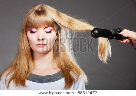 Woman Making Hairstyle With Hair Iron