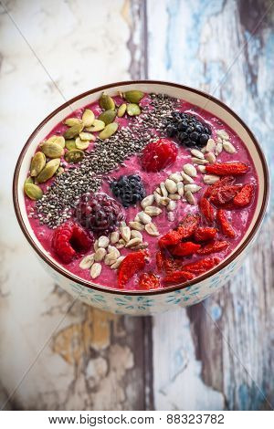 Breakfast berry smoothie bowl topped with goji berries,raspberry, blackberry, pumpkin, sunflower and chia seeds.