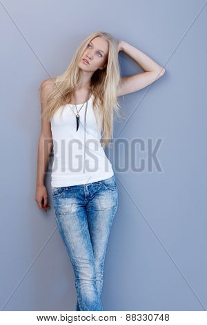 Pretty young blonde woman posing by wall in jeans and top.