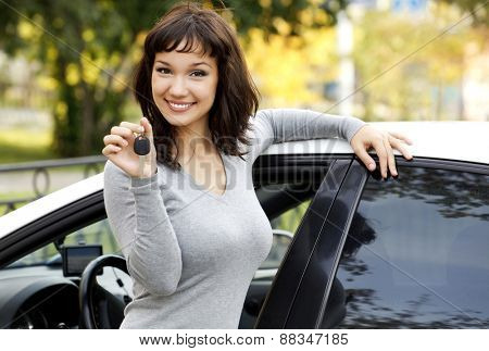 Pretty girl in a car showing the key.