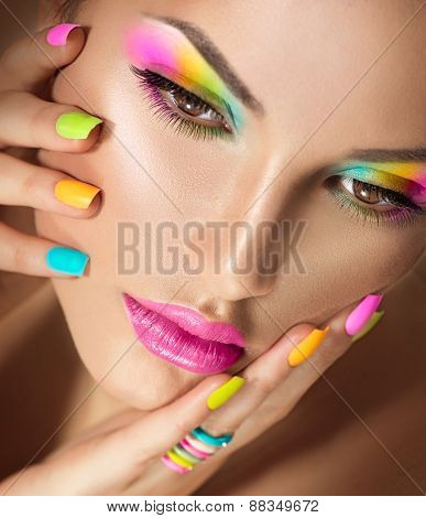 Beauty Girl face with Vivid Makeup and colorful Nail polish. Colourful nails. Fashion Woman portrait close up. Bright Colors. Long eyelashes, vivid eyeshadows Rainbow make up