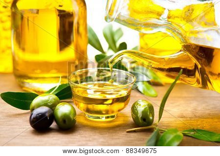 Olive Oil. Pouring Virgin Olive Oil in a bowl close up. Olives and Healthy Olive oil being poured from glass bottle. Diet. Bottle of olive oil. Dieting concept. Healthy food