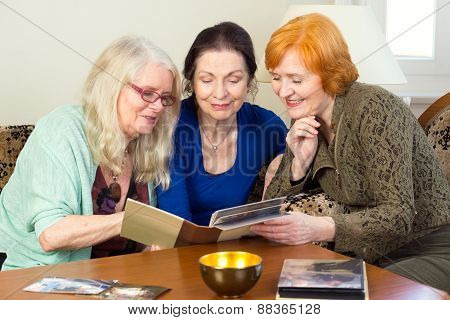 Middle Age Female Friends Looking At Photo Album