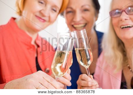 Smiling Mom Friends Tossing Glasses Of Champagne