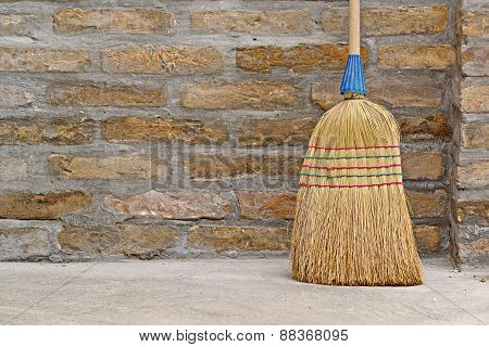 Household Broom For Floor Cleaning Leaning On Brick Wall