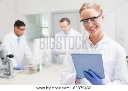 Smiling scientist using tablet while colleagues working behind in laboratory
