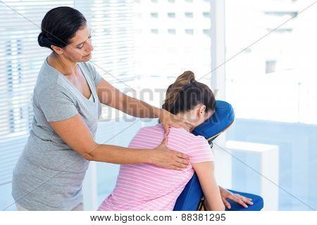 Woman having shoulders massage in medical office